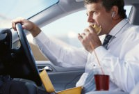 man eating in car
