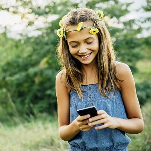 Girl outside with flowers in her hair texting on cell phone, Pla